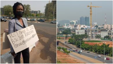 Frustrated Nigerian lady hits Abuja street with cardboard to beg for job, her photo stirs reactions
